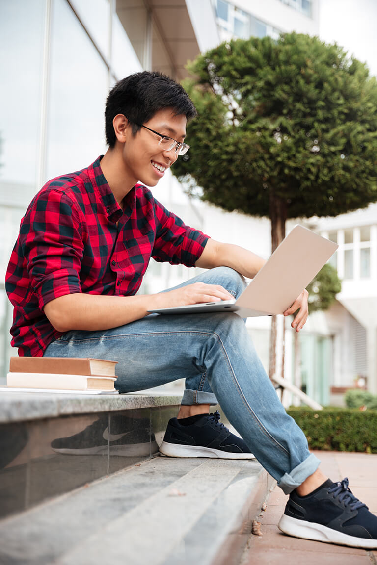 cheerful-asian-young-man-sitting-and-using-laptop-PTGSMW2